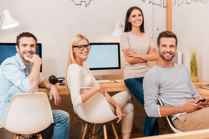 41248722 - confident business team. group of cheerful business people in smart casual wear sitting at the desk together and smiling